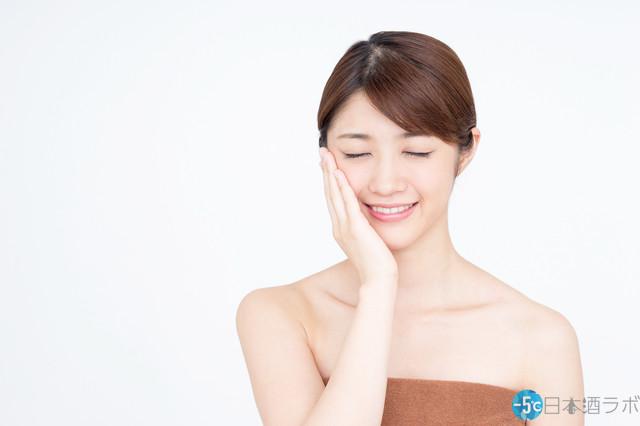 笑顔で頬に手を当てる女性