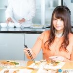 美味しそうに食べ物を箸でとる女性